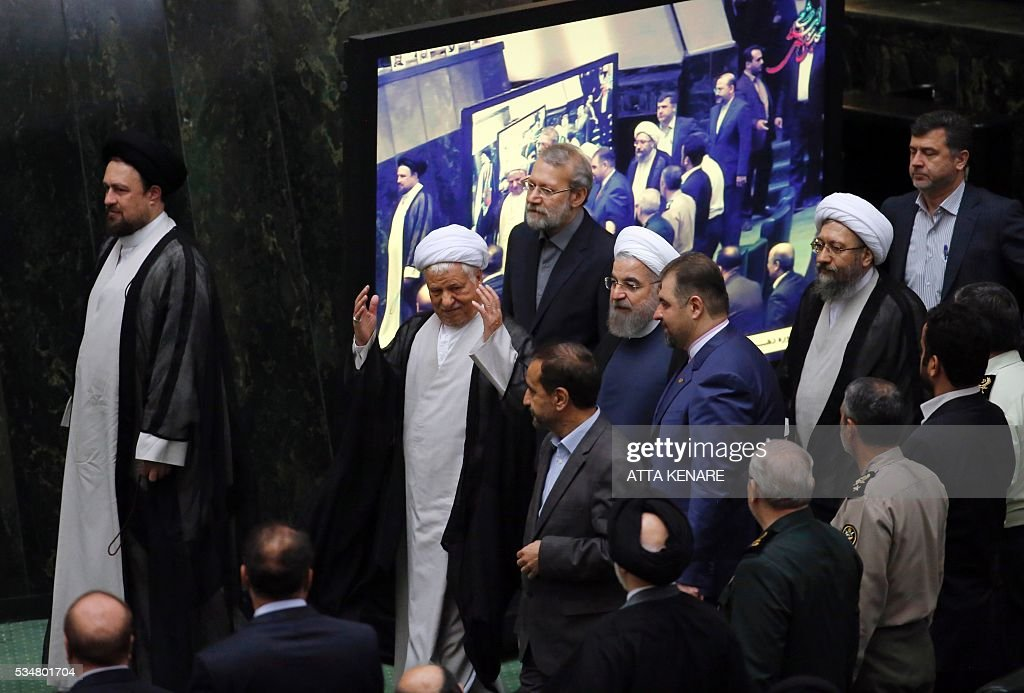 Iranian President Hasan Rouhani (C) walks alongside former president Ayatollah Akbar Hashemi Rafsanjani (C-L), Parliament Speaker Ali Larijani (C-top) and Judiciary Chief Sadeq Larijani (2nd from R) as they attend the opening session of the new parliament in Tehran on May 28, 2016. Iranian parliamentarians met in Tehran for the first time since elections finished in April. KENARE