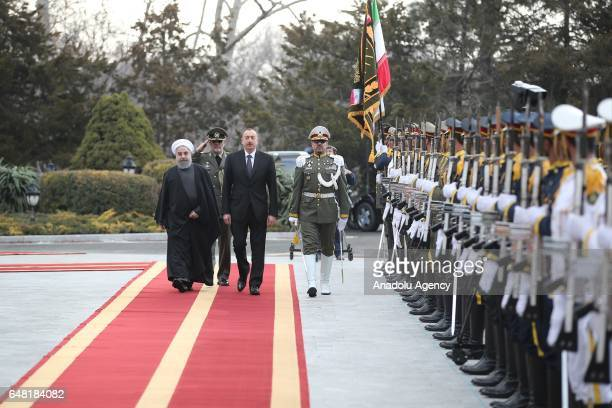 Iranian President Hassan Rouhani and Azerbaijan's President Ilham Aliyev walk past honor guards during an official welcoming ceremony in Tehran Iran...