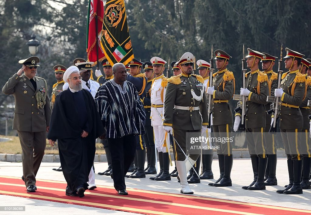 Iranian President Hassan Rouhani (L) and Ghana's president John Dramani Mahama review the honour guard during a welcoming ceremony before a meeting at the Saadabad Palace on February 14, 2016 in Tehran. / AFP / ATTA KENARE