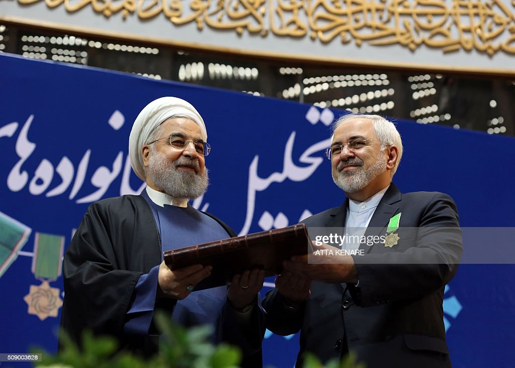 Iranian President Hassan Rouhani (L) awards Foreign Minister Mohammad Javad Zarif with the Medal of Honour for his role in the implementation of a nuclear deal with world powers, on February 8, 2016, in Tehran. / AFP / ATTA KENARE