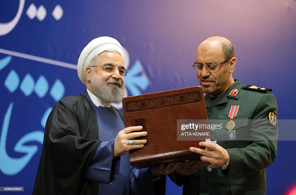 Iranian President Hassan Rouhani (L) awards Iran's Defence Minister Hossein Dehghan with the Medal of Honour for his role in the implementation of a nuclear deal with world powers, on February 8, 2016, in Tehran. / AFP / ATTA KENARE