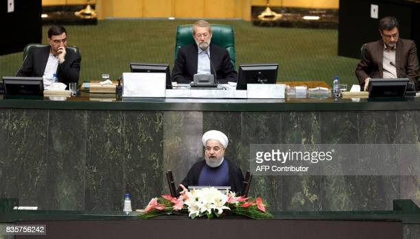 Iranian President Hassan Rouhani delivers a speach to the parliament in Tehran on August 20 as Iran's parliament prepares to vote on the president's...