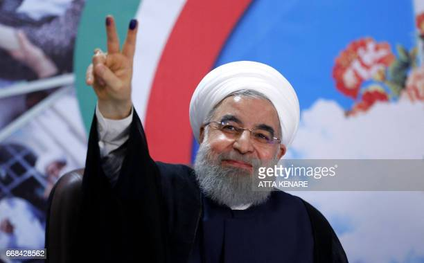 Iranian President Hassan Rouhani gestures to the camera after registering to run for reelection at the interior ministry in the capital Tehran on...