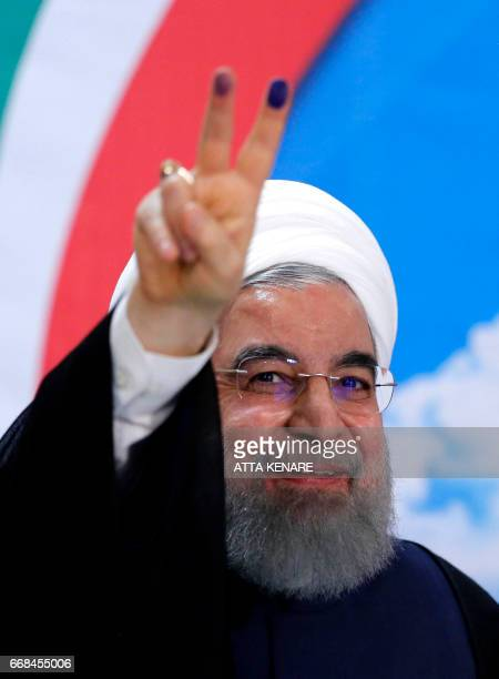 Iranian President Hassan Rouhani gestures with the sign for victory after registerimg to run for reelection at the interior ministry in the capital...