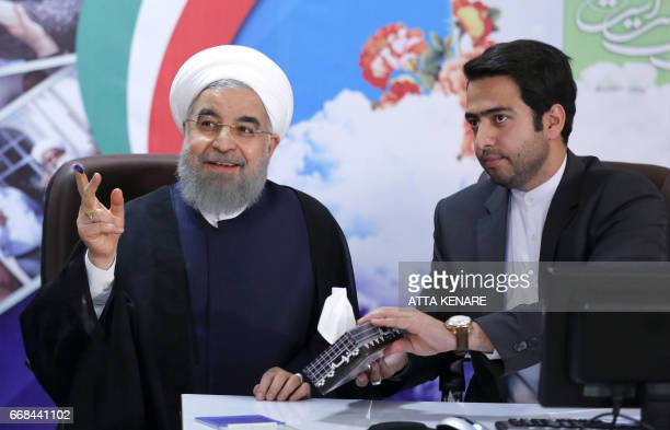 Iranian President Hassan Rouhani is handed tissues after registering to run for reelection at the interior ministry in the capital Tehran on April 14...