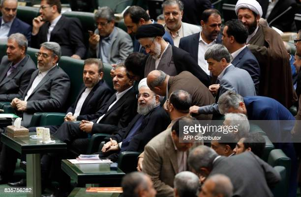 Iranian President Hassan Rouhani listen to his advisors upon arriving at the parliament in Tehran on August 20 as Iran's parliament prepares to vote...