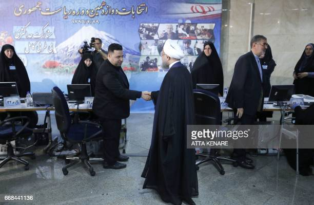 Iranian President Hassan Rouhani shakes hands with another candidate after registering to run for reelection at the interior ministry in the capital...