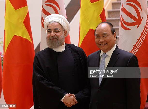 Iranian President Hassan Rouhani shakes hands with Vietnamese Prime Minister Nguyen Xuan Phuc as they meet at Phuc's Cabinet Office in Hanoi on...
