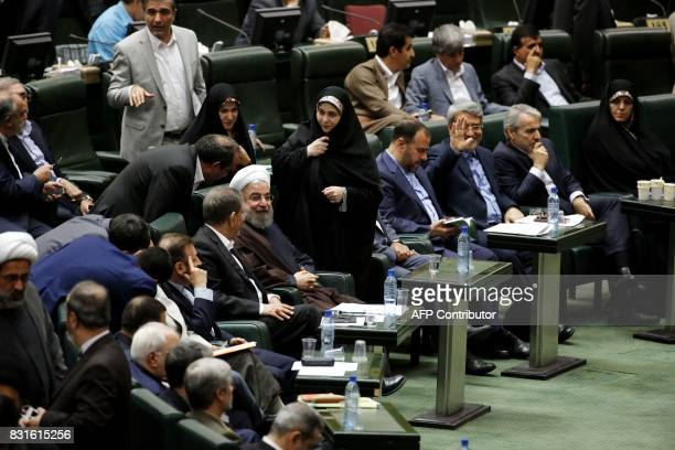 Iranian President Hassan Rouhani sits among parliament members after addressing the parliament in the capital Tehran on August 15 2017 Rouhani warned...