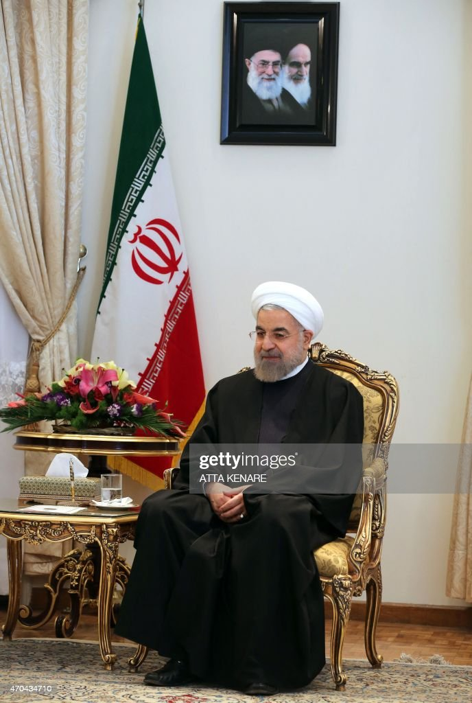 Iranian President Hassan Rouhani sits under portraits of Iran's supreme leader, Ayatollah Ali Khamenei (L) and Iran's founder of Islamic Republic, Ayatollah Ruhollah Khomeini (R), during his meeting with Venezuelan Foreign Minister Delcy Rodriguez in the Iranian capital, Tehran, on April 20, 2015.