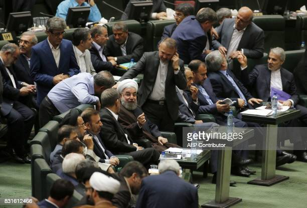 Iranian President Hassan Rouhani talks to parliament members after addressing the parliament in the capital Tehran on August 15 2017 Rouhani warned...