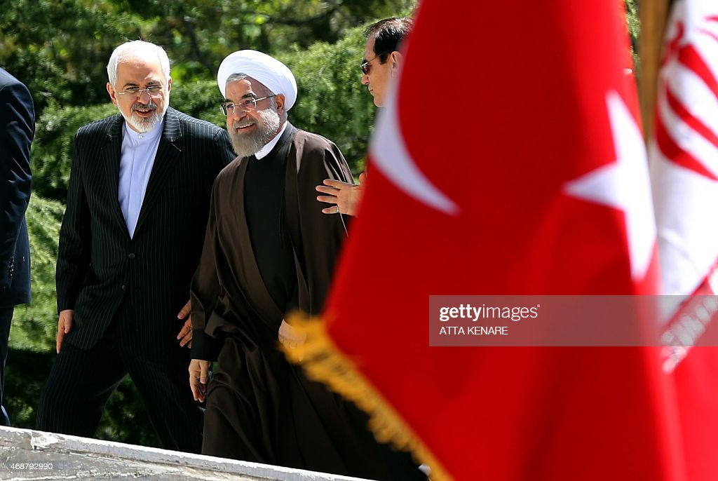 Iranian President Hassan Rouhani talks with his Foreign Minister Mohammad Javad Zarif as they arrive for a welcome ceremony for Turkish President at...