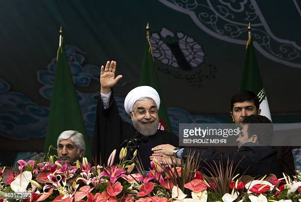 Iranian President Hassan Rouhani waves to the crowd during a rally in Tehran's Azadi Square to mark the 36th anniversary of the Islamic revolution on...