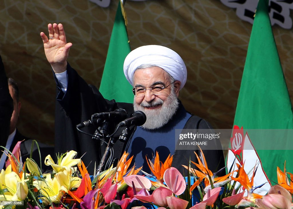 Iranian President Hassan Rouhani waves to the crowd during a rally in Tehran's Azadi Square (Freedom Square) to mark the 37th anniversary of the Islamic revolution on February 11, 2016. / AFP / ATTA KENARE