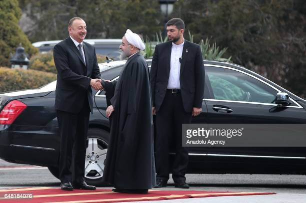 Iranian President Hassan Rouhani welcomes as he shakes hands with Azerbaijan's President Ilham Aliyev before they hold a joint press conference...