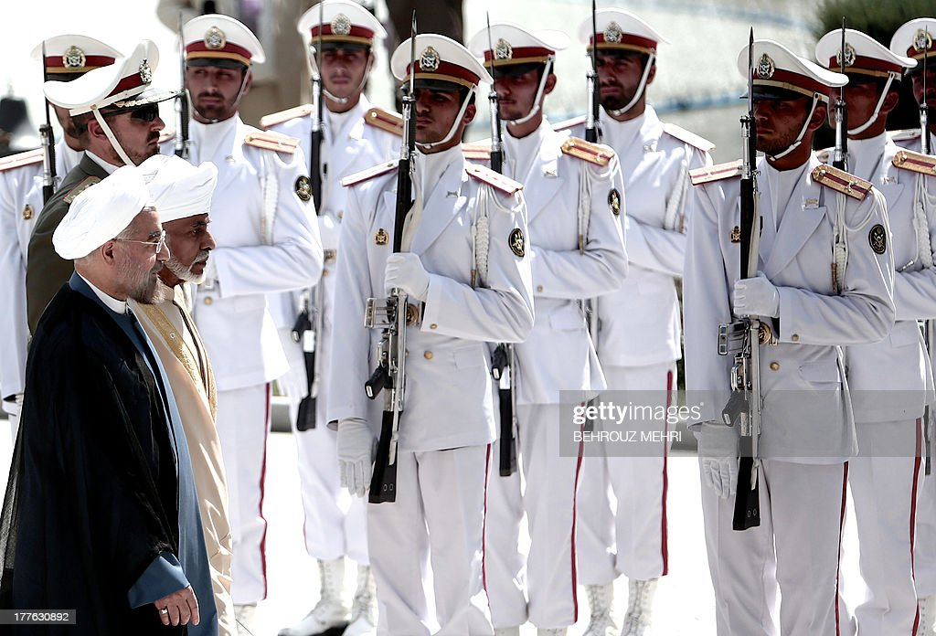 Iranian President Hassan Rowhani (L) and Oman's Sultan Qaboos bin Said (2nd-L) review the honour guard during the latter's welcoming ceremony at Tehran's Saadabad Palace on August 25, 2013. The Iranian authorities have announced that Sultan Qaboos of Oman, the only Gulf leader to maintain good relations with Tehran, arrived in Iran for a focus on economic issues and diplomacy visit. AFP PHOTO/BEHROUZ MEHRI