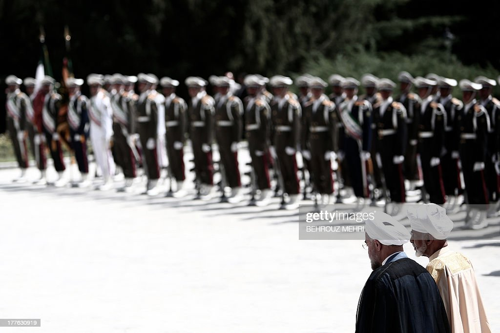 Iranian President Hassan Rowhani (L) and Oman's Sultan Qaboos bin Said (R) review the honour guard during the latter's welcoming ceremony at Tehran's Saadabad Palace on August 25, 2013. The Iranian authorities have announced that Sultan Qaboos of Oman, the only Gulf leader to maintain good relations with Tehran, arrived in Iran for a focus on economic issues and diplomacy visit.