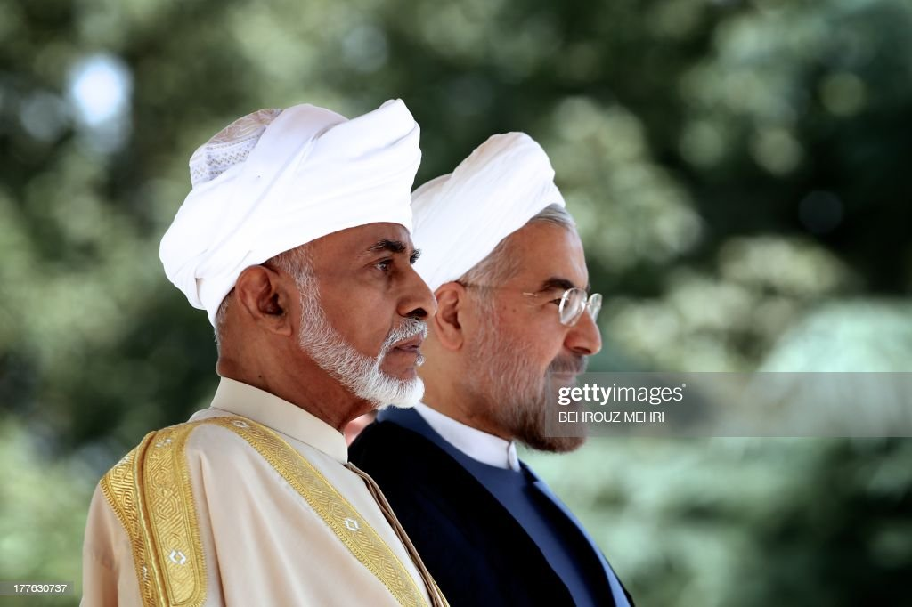 Iranian President Hassan Rowhani (R) and Oman's Sultan Qaboos bin Said (L) listen to the national anthems during a welcome ceremony at Tehran's Saadabad Palace on August 25, 2013. The Iranian authorities have announced that Sultan Qaboos of Oman, the only Gulf leader to maintain good relations with Tehran, arrived in Iran for a focus on economic issues and diplomacy visit. AFP PHOTO/BEHROUZ MEHRI