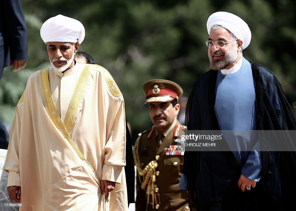 Iranian President Hassan Rowhani (R) walks with Oman's Sultan Qaboos bin Said (L) during a welcome ceremony at Tehran's Saadabad Palace on August 25, 2013. The Iranian authorities have announced that Sultan Qaboos of Oman, the only Gulf leader to maintain good relations with Tehran, arrived in Iran for a focus on economic issues and diplomacy visit. AFP PHOTO/BEHROUZ MEHRI