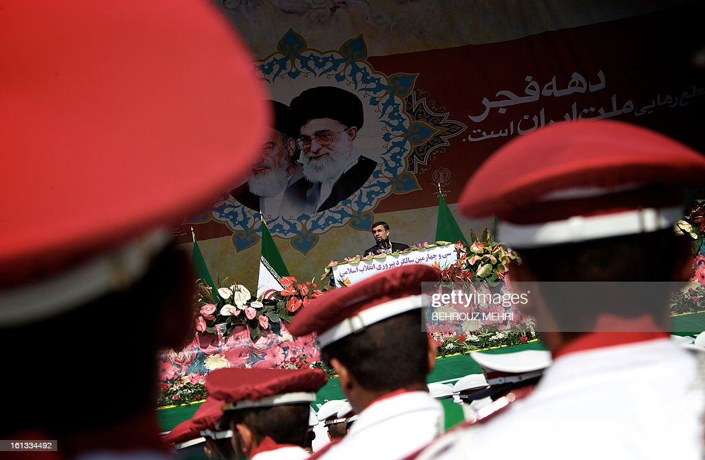 Iranian President Mahmoud Ahmadinejad delivers a speech as he stands under portraits of late founder of Islamic Republic, Ayatollah Ruhollah Khomeini (L) and supreme leader, Ayatollah Ali khamenei (R) during a rally in Tehran's Azadi Square (Freedom Square) to mark the 34th anniversary of the Islamic revolution on February 10, 2013. Hundreds of thousands of people marched in Tehran and other cities chanting 'Death to America' and 'Death to Israel' as Iran celebrated the anniversary of the ousting of the US-backed shah. AFP PHOTO/BEHROUZ MEHRI