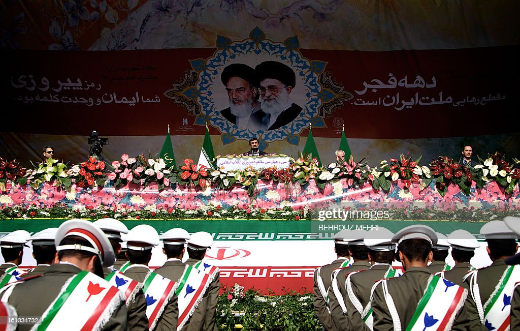 Iranian President Mahmoud Ahmadinejad (C) delivers a speech as he stands under portraits of late founder of Islamic Republic, Ayatollah Ruhollah Khomeini (L) and supreme leader, Ayatollah Ali khamenei (R) during a rally in Tehran's Azadi Square (Freedom Square) to mark the 34th anniversary of the Islamic revolution on February 10, 2013. Hundreds of thousands of people marched in Tehran and other cities chanting 'Death to America' and 'Death to Israel' as Iran celebrated the anniversary of the ousting of the US-backed shah. AFP PHOTO/BEHROUZ MEHRI