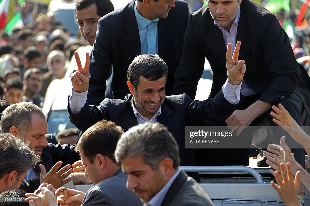 Iranian President Mahmoud Ahmadinejad (C) flashes the sign for victory as he greets supporters during a rally in Tehran's Azadi Square (Freedom Square) to mark the 34th anniversary of the Islamic revolution on February 10, 2013. Hundreds of thousands of people marched in Tehran and other cities chanting 'Death to America' and 'Death to Israel' as Iran celebrated the anniversary of the ousting of the US-backed shah. AFP PHOTO / ATTA KENARE