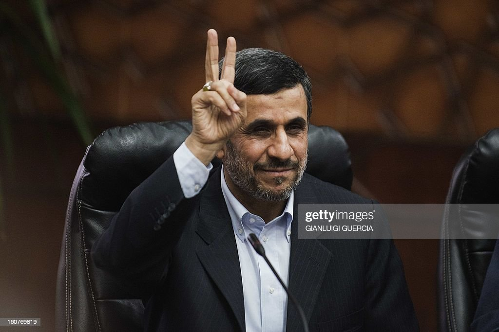 Iranian President Mahmoud Ahmadinejad flashes the victory sign ahead of a meeting Ahmed al-Tayyeb, the grand imam of Cairo's Al-Azhar, Sunni Islam's highest seat of learning, in Cairo on February 5, 2013. Ahmadinejad was told not to interfere in the security of Gulf Arab nations and to respect the rights of his country's Sunni minority as he began a landmark visit to Egypt. AFP PHOTO/GIANLUIGI GUERCIA