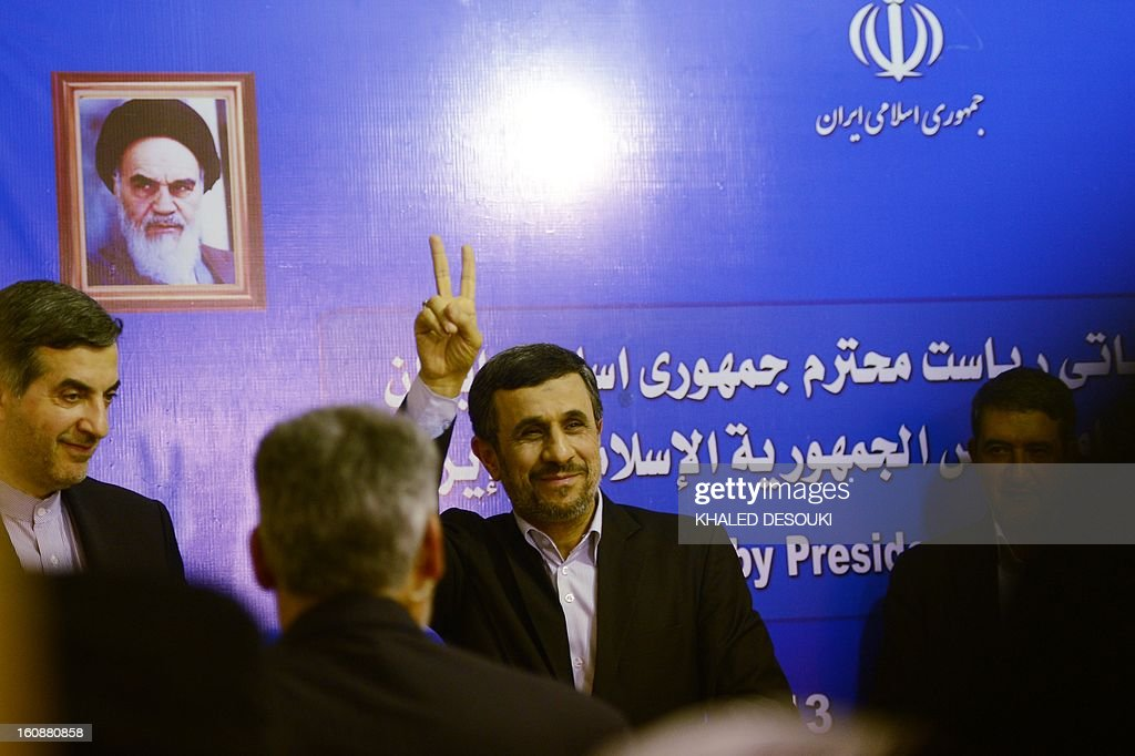 Iranian President Mahmoud Ahmadinejad flashes the victory sign as he leaves after his press conference at the residence of the Iranian ambassador to Egypt in Cairo on February 7, 2013. Ahmadinejad is in Cairo to attend the Organisation of Islamic Cooperation summit.