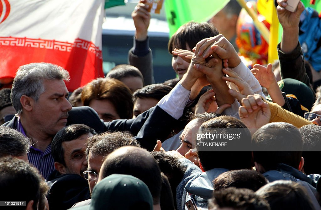 Iranian President Mahmoud Ahmadinejad (bottom-L) greets supporters during a rally in Tehran's Azadi Square (Freedom Square) to mark the 34th anniversary of the Islamic revolution on February 10, 2013. Hundreds of thousands of people marched in Tehran and other cities chanting 'Death to America' and 'Death to Israel' as Iran celebrated the anniversary of the ousting of the US-backed shah. AFP PHOTO / ATTA KENARE