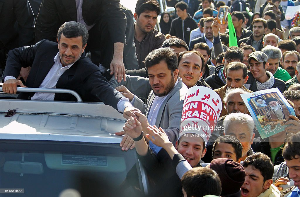 Iranian President Mahmoud Ahmadinejad (L) greets supporters during a rally in Tehran's Azadi Square (Freedom Square) to mark the 34th anniversary of the Islamic revolution on February 10, 2013. Hundreds of thousands of people marched in Tehran and other cities chanting 'Death to America' and 'Death to Israel' as Iran celebrated the anniversary of the ousting of the US-backed shah.