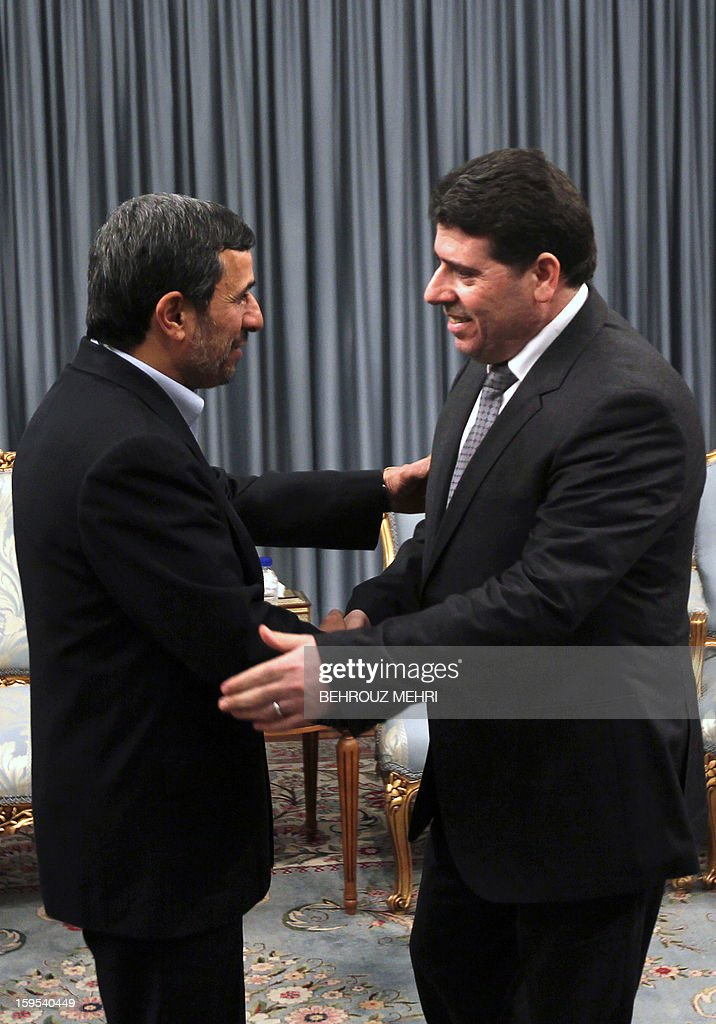Iranian President Mahmoud Ahmadinejad (L) greets Syrian Prime Minister Wael al-Halaqi (R) prior to a meeting in Tehran on January 15, 2013. Fars news agency said the two sides will discuss 'expansion of bilateral relations and Syrian President Bashar al-Assad's three-step plan' for the political future, presented on January 6.
