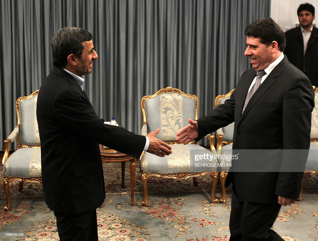 Iranian President Mahmoud Ahmadinejad (L) greets Syrian Prime Minister Wael al-Halaqi (R) prior to a meeting in Tehran on January 15, 2013. Fars news agency said the two sides will discuss 'expansion of bilateral relations and Syrian President Bashar al-Assad's three-step plan' for the political future, presented on January 6. AFP PHOTO/BEHROUZ MEHRI