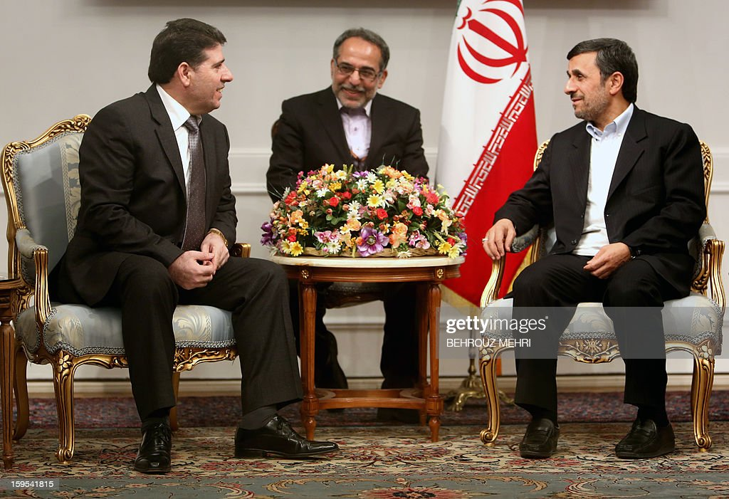 Iranian President Mahmoud Ahmadinejad (R) greets Syrian Prime Minister Wael al-Halaqi (L) prior to a meeting in Tehran on January 15, 2013. Fars news agency said the two sides will discuss 'expansion of bilateral relations and Syrian President Bashar al-Assad's three-step plan' for the political future, presented on January 6. AFP PHOTO/BEHROUZ MEHRI