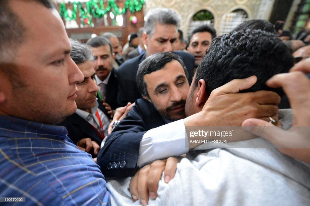 Iranian President Mahmoud Ahmadinejad (C) kisses an Egyptian man during his visit to the Sayyeda Zeinab mosque in the Egyptian capital Cairo, on February 5, 2013. Ahmadinejad held talks in Cairo on the divisive issue of Syria's war, as he kicked off the first visit to Egypt by an Iranian president since 1979. AFP PHOTO / KHALED DESOUKI