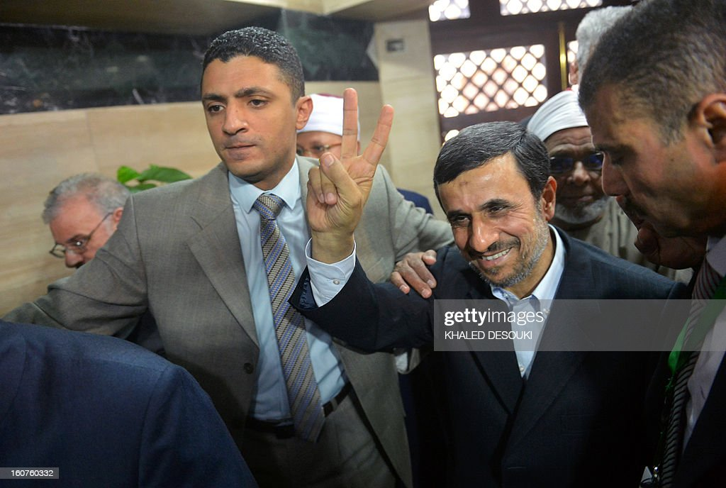 Iranian President Mahmoud Ahmadinejad (2nd-R) makes the victory sign upon his arrival for a visit to Al-Azhar headquarters in Cairo on February 5, 2013. Ahmadinejad held talks in Cairo on the divisive issue of Syria's war, as he kicked off the first visit to Egypt by an Iranian president since 1979. AFP PHOTO / KHALED DESOUKI