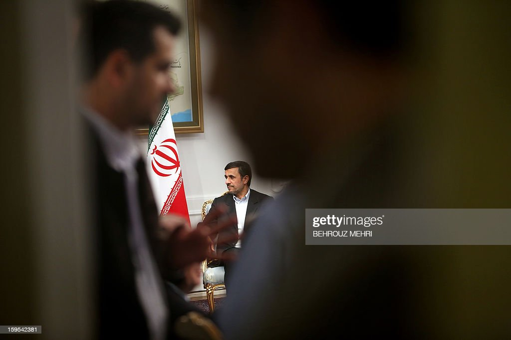 Iranian President Mahmoud Ahmadinejad (C) meets with Syrian Prime Minister Wael al-Halaqi (unseen) in Tehran on January 15, 2013. Fars news agency said the two sides will discuss 'expansion of bilateral relations and Syrian President Bashar al-Assad's three-step plan' for the political future, presented on January 6.
