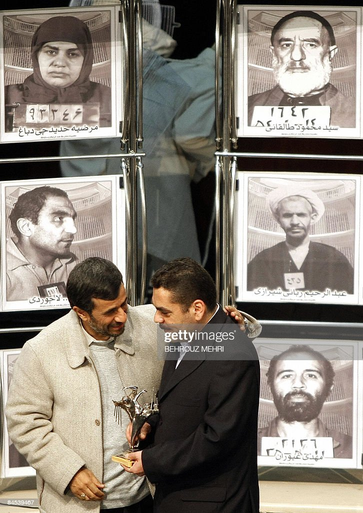Iranian President Mahmoud Ahmadinejad (L) presents a statue to Lebanese militant and convicted murderer, Samir Kantar (R), during a ceremony in Tehran on January 29, 2009, to honour the political prisoners (portraits) of the shah's regime before the Islamic revolution. Kantar, who was controversially freed by Israel in a prisoner swap last year, called for the destruction of Israel during a visit to Tehran where he was greeted by Ahmadinejad and honoured with the presentation of a statue of two prisoners trying to break through the bars of a jail cell. AFP PHOTO/BEHROUZ MEHRI