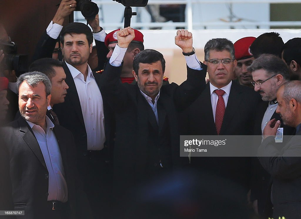 Iranian President Mahmoud Ahmadinejad raises his hands toward cheering supporters while standing next to Venezuela's Foreign Minister Elias Jaua as...