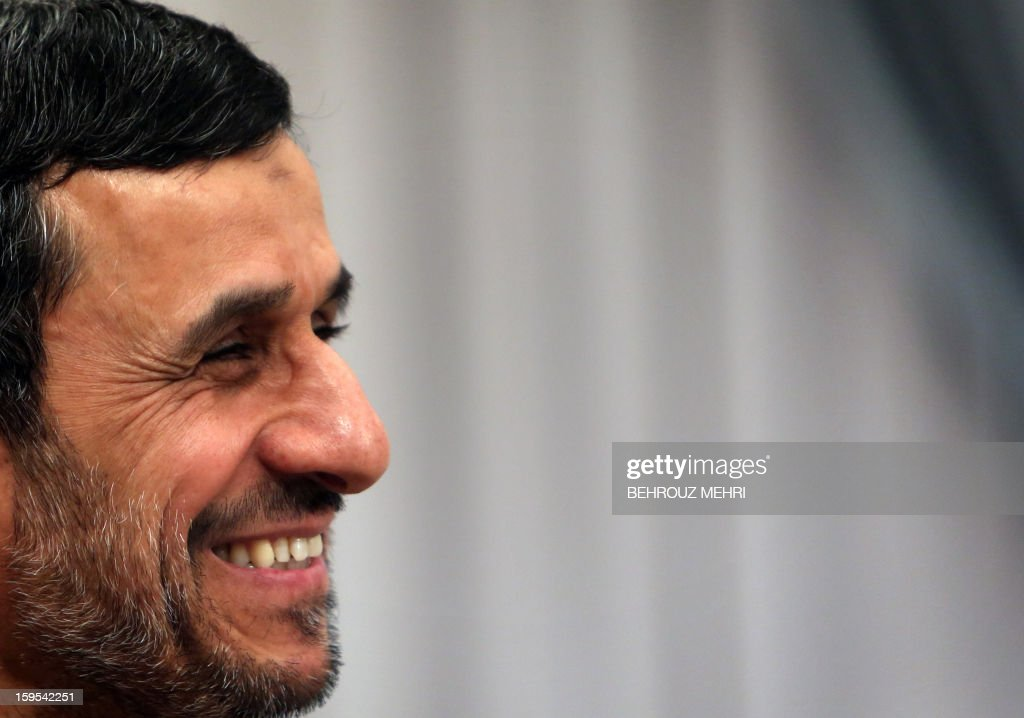 Iranian President Mahmoud Ahmadinejad smiles as he attends a meeting with Syrian Prime Minister Wael al-Halaqi in Tehran on January 15, 2013. Fars news agency said the two sides will discuss 'expansion of bilateral relations and Syrian President Bashar al-Assad's three-step plan' for the political future, presented on January 6. AFP PHOTO/BEHROUZ MEHRI