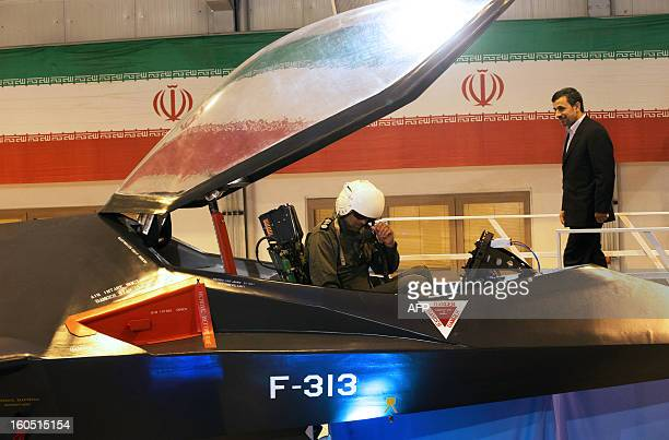 Iranian President Mahmoud Ahmadinejad walks to talk with the pilot of the domestically designed and built Qaher F313 fighter jet during a ceremony to...
