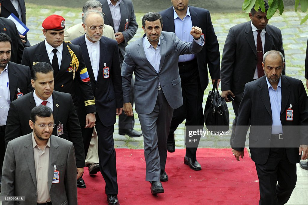 Iranian President Mahmud Ahmadinejad (C) raises his clenched fist upon arrival at the National Assembly for the installation of Venezuelan President Nicolas Maduro in Caracas on April 19, 2013.