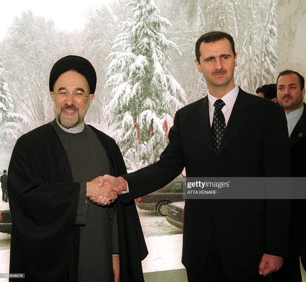 Iranian President Mohammad Khatami (L) shakes hands with Syrian President Bashar al-Assad at Tehran's Saad Abad presidential palace 25 January 2001. Assad ended a two-day visit, his first to the Islamic Republic since taking power six months ago, after talks with Khatami and Iran's supreme leader Ayatollah Ali Khamenei. (Film) AFP PHOTO/Atta KENARE