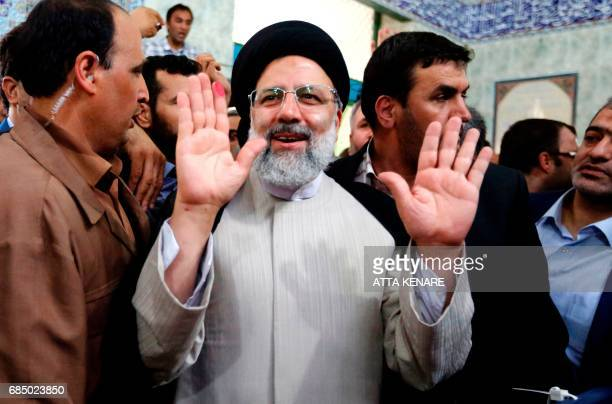 Iranian presidential candidate Ebrahim Raisi gestures after casting his ballot for the presidential elections at a polling station in southern Tehran...