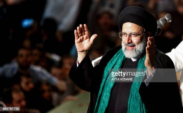 Iranian presidential candidate Ebrahim Raisi greets his supporters during a campaign rally at Imam Khomeini Mosque in the capital Tehran on May 16...