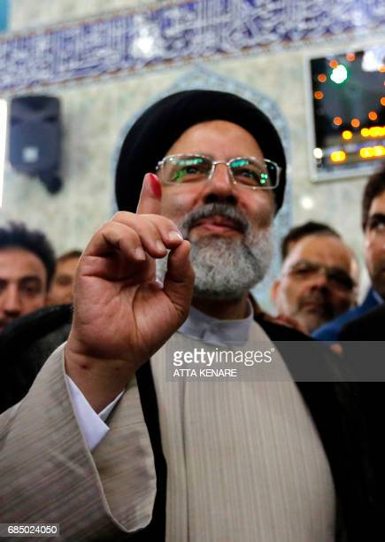 Iranian presidential candidate Ebrahim Raisi shows inkstained finger after casting his ballot for the presidential elections at a polling station in...