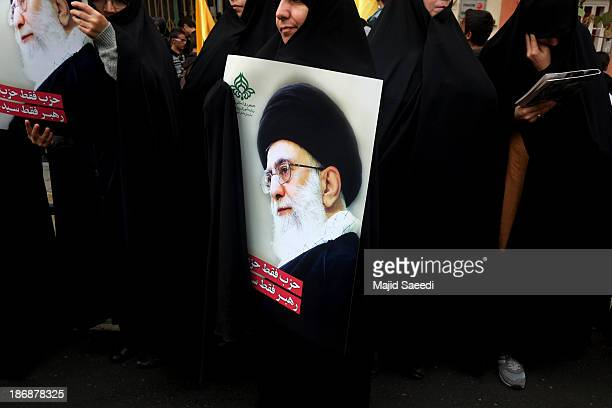 Iranian protester holds a photo of supreme leader Ayatollah Ali Khamenei during a demonstration to mark the 34th anniversary of the 1979 US embassy...