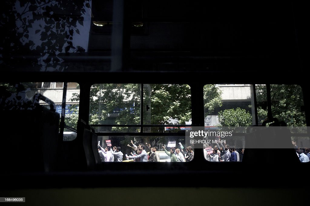 Iranian protesters are seen through the windows of a bus as they shout slogans during an anti-Israeli demonstration at Palestine Square in Tehran after the weekly Friday prayers on May 10, 2013 to condemn last week's Israeli air strikes near the Syrian capital Damascus. Iran has condemned the Israeli strikes and said it is ready to train the Syrian army, which is in its third year of a conflict against rebels seeking to overthrow Bashar al-Assad. AFP PHOTO/BEHROUZ MEHRI