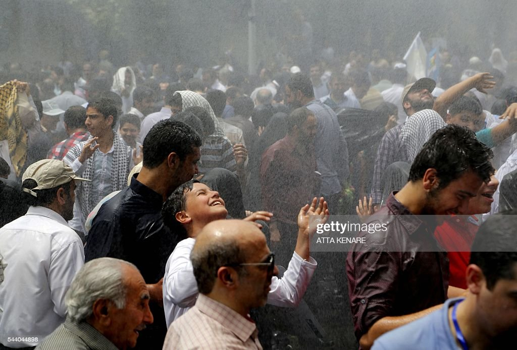 Iranian protesters cool themselves off under sprinkle water as the temperature reached 42 degrees Celsius in Tehran during a parade marking al-Quds (Jerusalem) Day on July 01, 2016. Tens of thousands joined pro-Palestinian rallies in Tehran, as the annual Quds Day protests take on broader meaning for a region mired in bitter disputes and war. KENARE