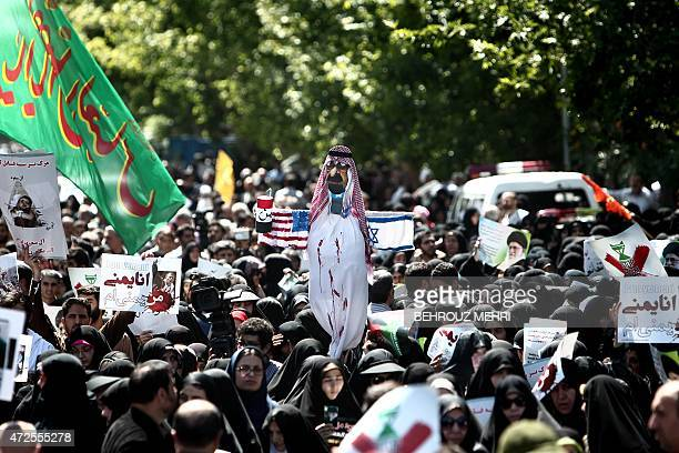 Iranian protesters hold an effigy of late Saudi King Abdullah with national flags of United States and Israel attached to it during a demonstration...