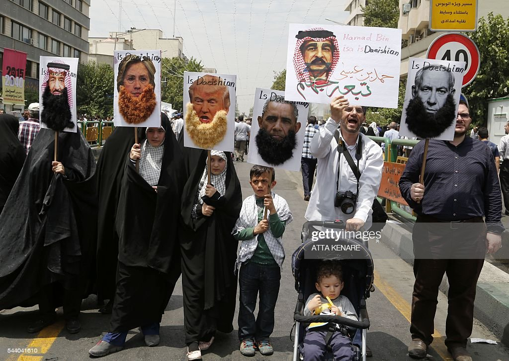 Iranian protesters hold portraits of (from L to R) Saudi King Salman, US Democrat presidential candidate Hillary Clinton, US Republican presidential candidate Donald Trump, US President Barack Obama, Bahraini King Hamad and Israeli Prime Minister Benjamin Netayahu, most adorned with jihad-style beards and a slogan reading 'is Daeishian' (Arabic acronym for Islamic State), during a parade marking al-Quds (Jerusalem) Day in Tehran on July 01, 2016. Tens of thousands joined pro-Palestinian rallies in Tehran, as the annual Quds Day protests take on broader meaning for a region mired in bitter disputes and war. KENARE